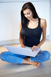 Young woman sitting on the floor using a laptop
