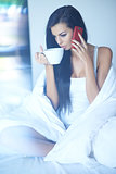 Woman drinking coffee as she talks on her mobile