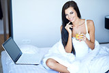 Smiling woman working on her laptop in bed