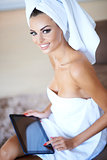 Woman Wearing Bath Towel Using Tablet Computer