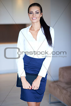 Beautiful elegant young woman holding a tablet