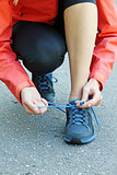 running and jogging exercising concept. woman tying laces
