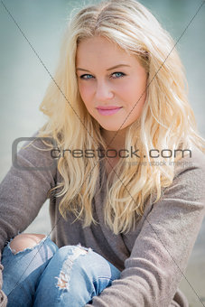 Blond woman sitting at lake
