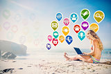 Composite image of gorgeous blonde in bikini using laptop on the beach