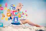 Composite image of pretty blonde sitting on beach using her laptop