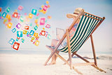 Composite image of woman in sunhat sitting on beach in deck chair using tablet pc