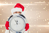 Composite image of festive woman holding clock