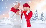 Composite image of happy winter couple with mugs