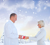 Composite image of couple exchanging gift