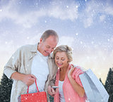 Composite image of couple with shopping bags and smartphone