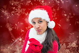 Composite image of festive brunette blowing