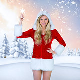 Composite image of pretty girl in santa outfit holding hand up