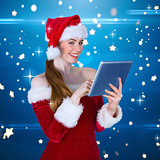 Composite image of pretty santa girl using tablet pc