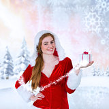 Composite image of pretty girl in santa costume holding gift box