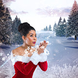 Composite image of pretty santa girl blowing over her hands
