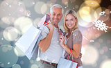 Composite image of happy couple with shopping bags and credit card