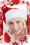 Composite image of young blonde woman putting on the santa claus hat