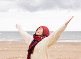 Composite image of woman in warm clothing stretching arms at beach