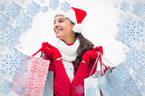 Composite image of beautiful festive woman holding shopping bags