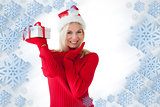 Composite image of festive blonde holding a present