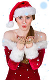 Composite image of pretty girl in santa costume blowing at camera