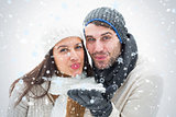 Composite image of attractive young couple in warm clothes blowing