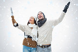 Composite image of attractive young couple in warm clothes with arms up