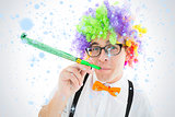 Composite image of geeky hipster wearing a rainbow wig blowing party horn