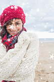 Composite image of cute smiling woman in stylish warm clothing on the beach