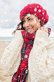Composite image of cute smiling woman in warm clothing looking away at beach