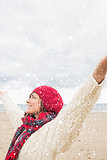 Composite image of woman in warm clothing stretching her arms at beach