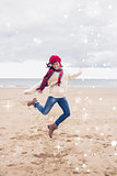 Composite image of woman in stylish warm clothing jumping at beach
