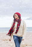 Composite image of woman in stylish warm clothing at beach
