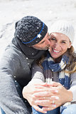 Composite image of attractive couple on the beach in warm clothing