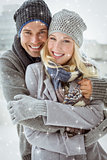 Composite image of cute couple in warm clothing smiling at camera