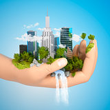 human hand holding a city on green grass hill with river, 3d