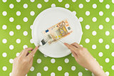 Woman eating fifty euroes banknotel for dinner