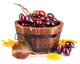 Fresh grapes in wooden basket with yellow leaf