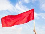 Hand waving a red flag with blue sky background