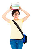 unhappy university student girl holding book on the head