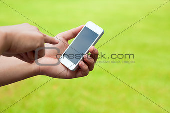 Touch screen mobile phone in hand with green meadow