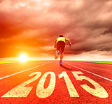 happy new year 2015. young man running with sunrise background