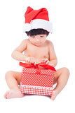 curious  baby in Santa cap looking at giftbox