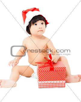 adorable baby in Santa cap sitting on floor with christmas gift