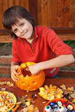 Boy preparing for Halloween - carving a jack-o-lantern