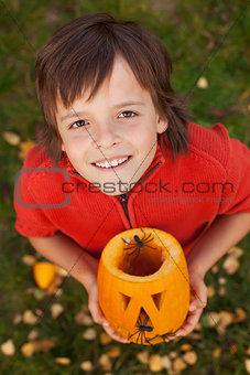 Boy with a Halloween pumpkin jack-o-lantern