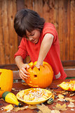 Boy busy carving a pumpkin jack-o-lantern for Halloween
