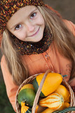 Little girl with a basketful of pumpkins