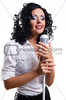 Beautiful young woman with headphones and microphone over white