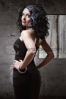 Beautiful woman wearing black dress posing indoors